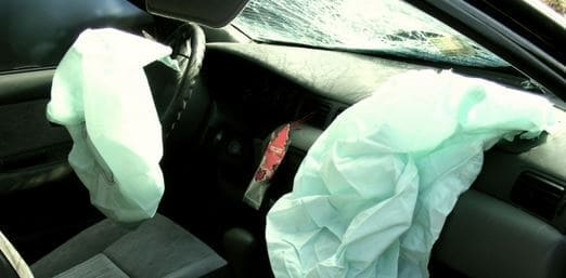 showing the front seats of a car that has been in an accident and the airbags have gone off