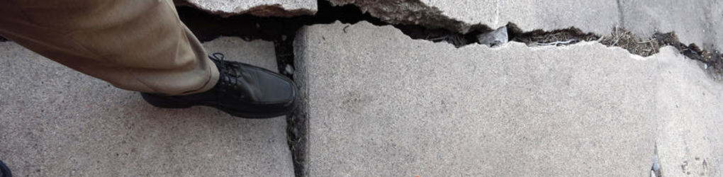 a person about to trip and fall from a crack in the sidewalk