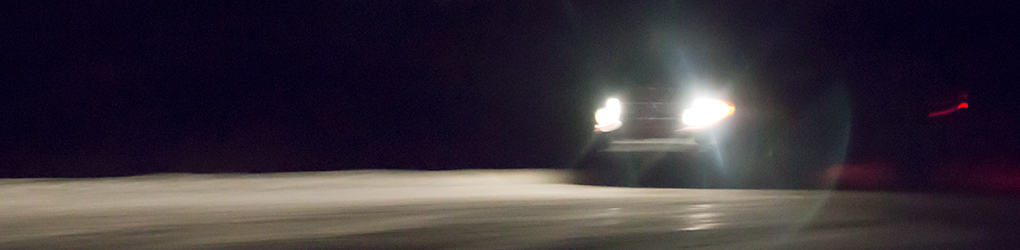 view of a car's headlights on while driving on a road in the dark