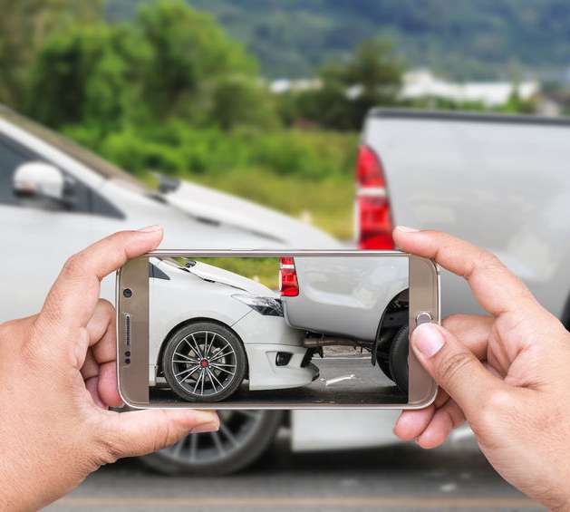 person taking a picture of a rear end car accident with their phone