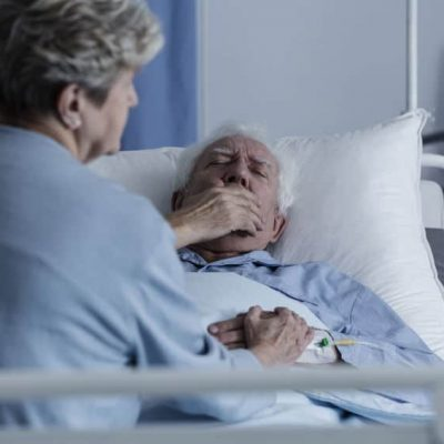 Elderly man with lung cancer lying in a hospital bed and coughing