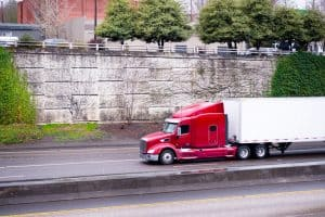 red semi truck driving down the road