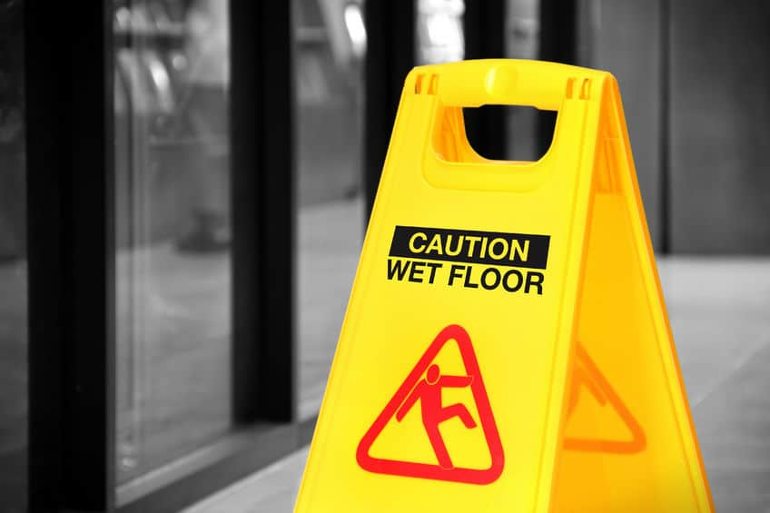 bright yellow caution sign of wet floor in a hallway. conceptual image with isolated color over black and white background