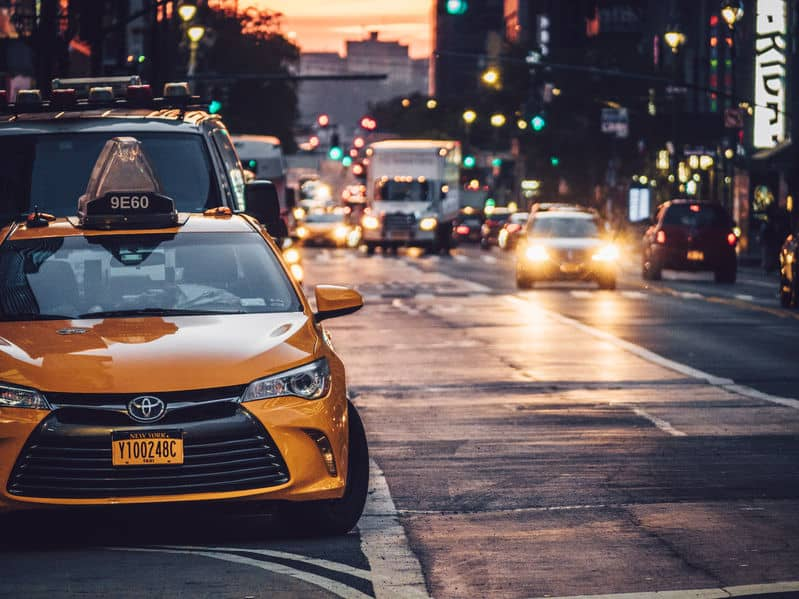 yellow taxi cab parked on the side of the road in new york city with traffic in the background