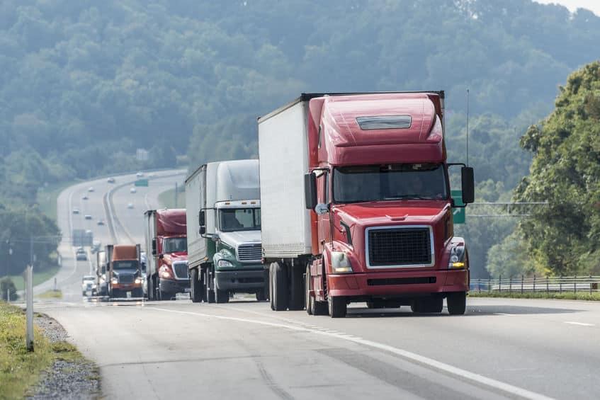line of semi trucks on the highway