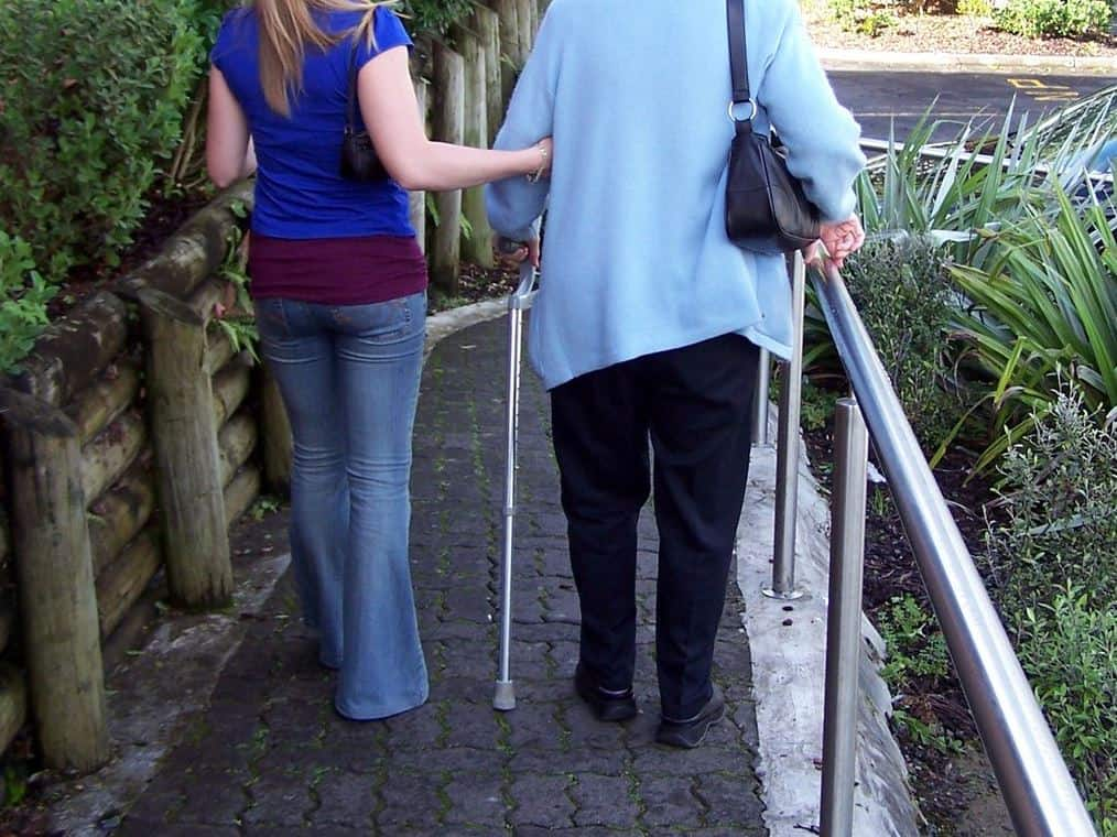 woman assisting an elderly woman walking with a can