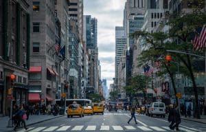 busy new york city street with traffic and pedestrians crossing in the crosswalk