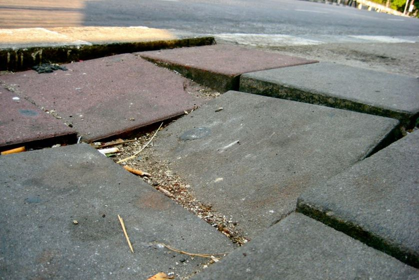close up of a broken and uneven sidewalk