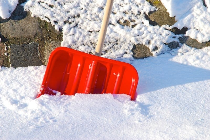 snow shovel halfway in a pile of snow