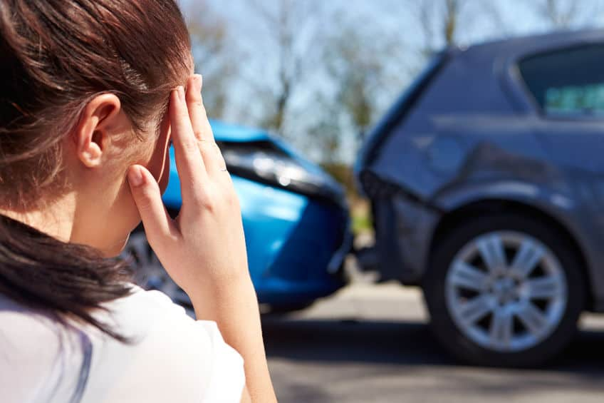 woman holding her head in pain after an injury with a car accident scene in the background