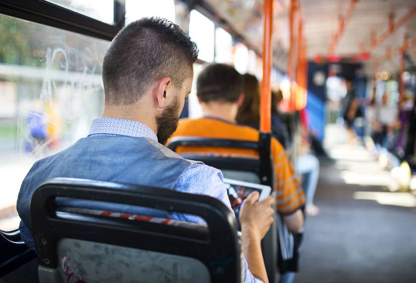 man looking at a tablet on a bus