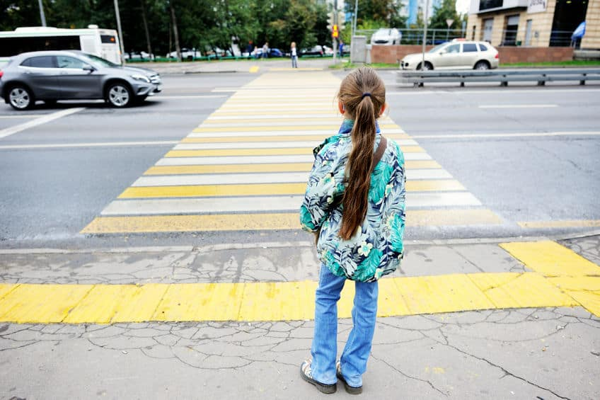 child crossing the road at a crosswalk
