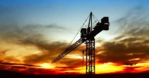 silhouette of a construction crane with a sunset in the background