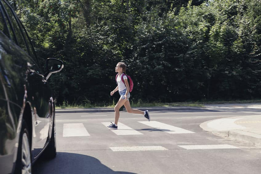 Girl wearing a backpack running through a pedestrian crossing in front of a car