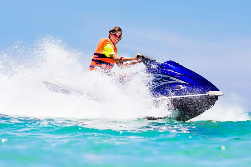 teenager jet skiing with a life jacket on