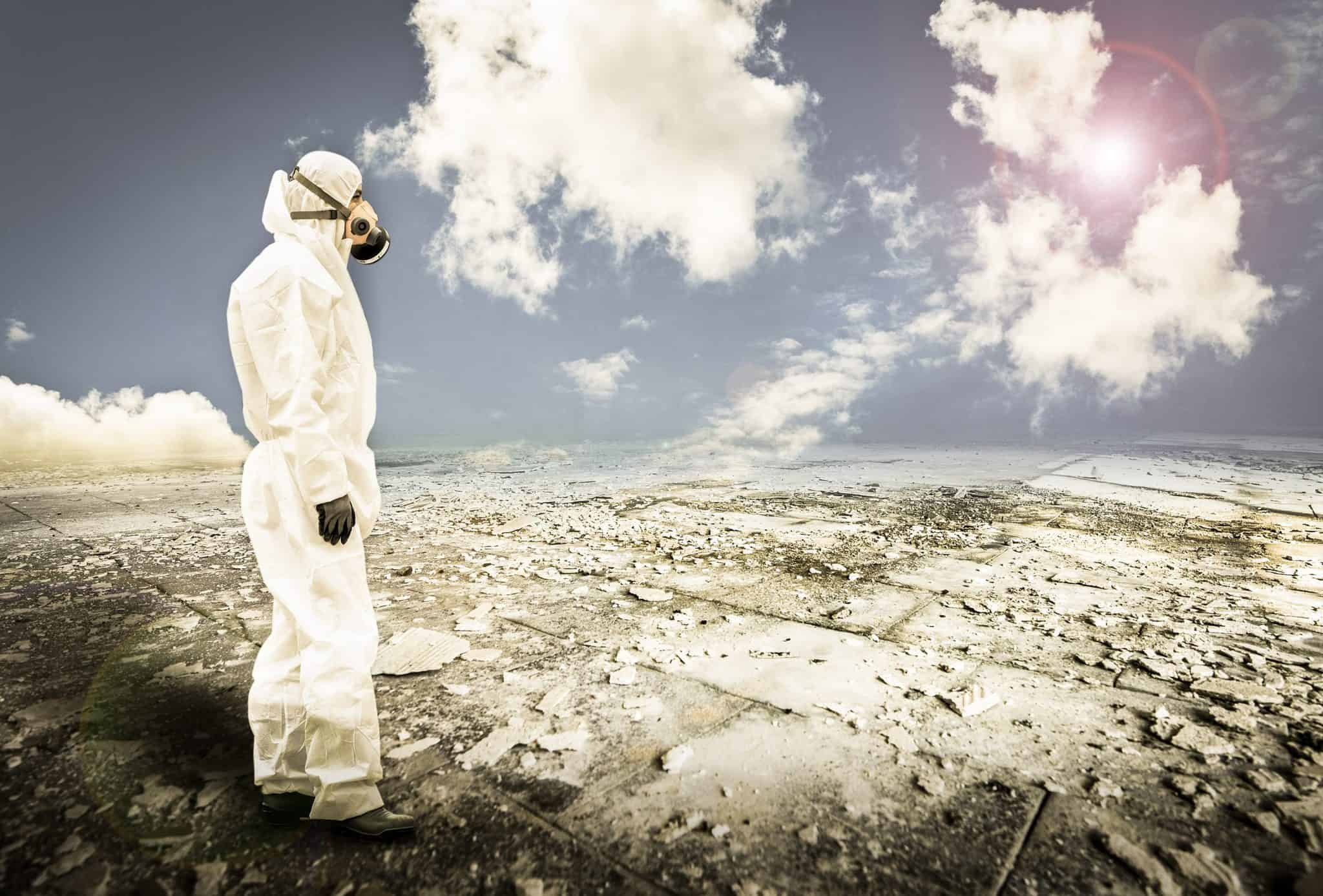 person in protective gear looking over a desolate area