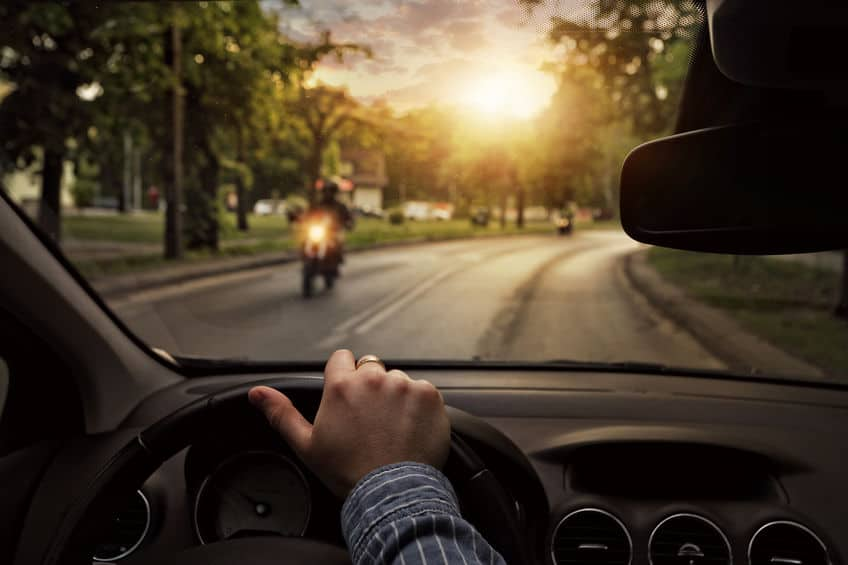 view from a driver of a car going towards a motorcyclist