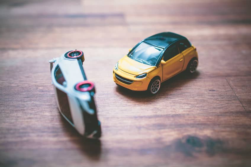 toy cars simulating an accident where on is flipped on its side