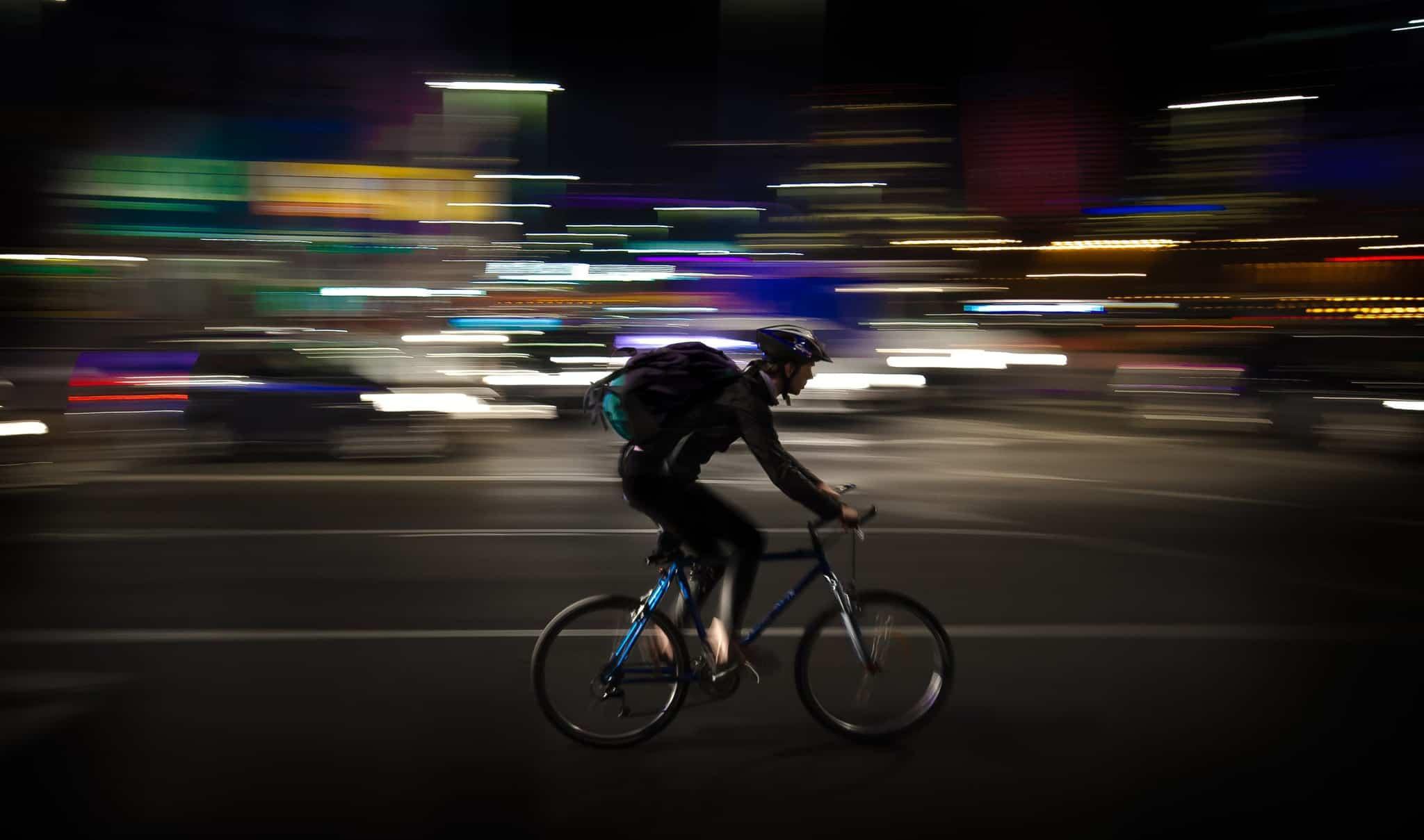 cyclist riding a bike with a blurred dark background