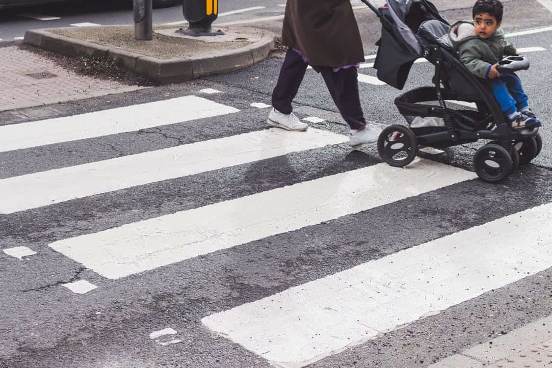 child being pushed in a stroller across a crosswalk