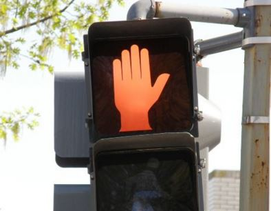 red stop sign hand lit up in a crosswalk