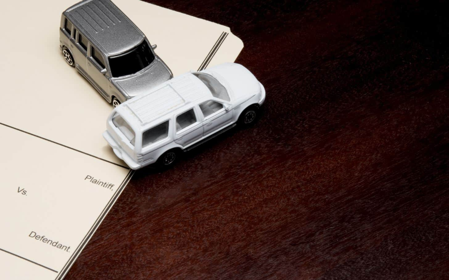 two toy cars demonstrating a t-bone crash on a desk and legal paperwork