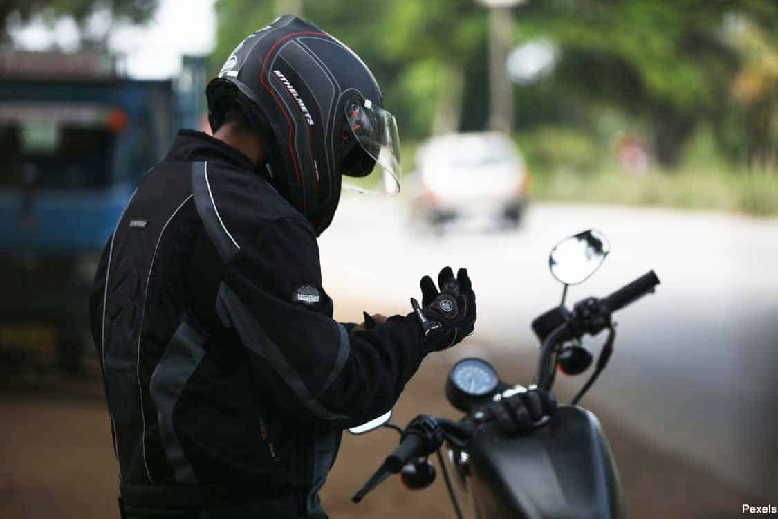 motorcyclist wearing a helmet and standing next to their bike fixing their glove