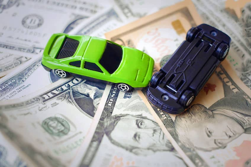 Toy cars demonstrating an accident on a background of 100 dollar bills