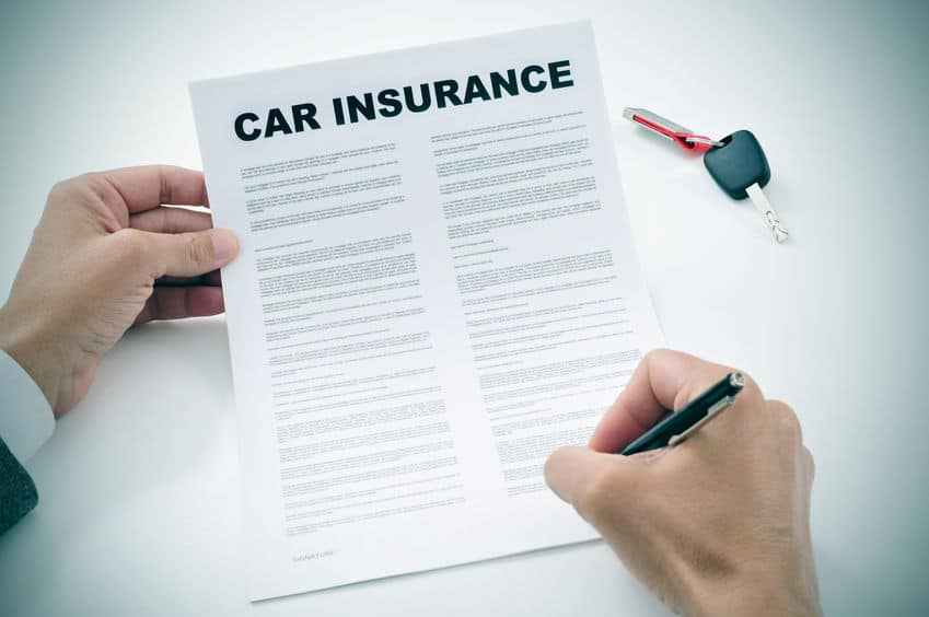 person signing a car insurance document