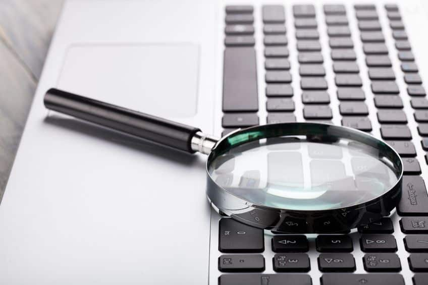laptop keyboard with magnifying glass on top of it