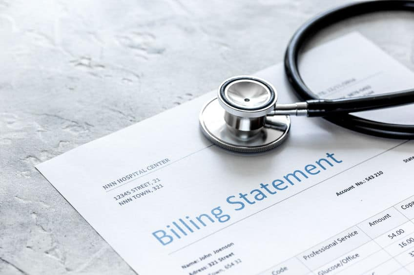 health care costs on a billing statement, stethoscope on stone table background