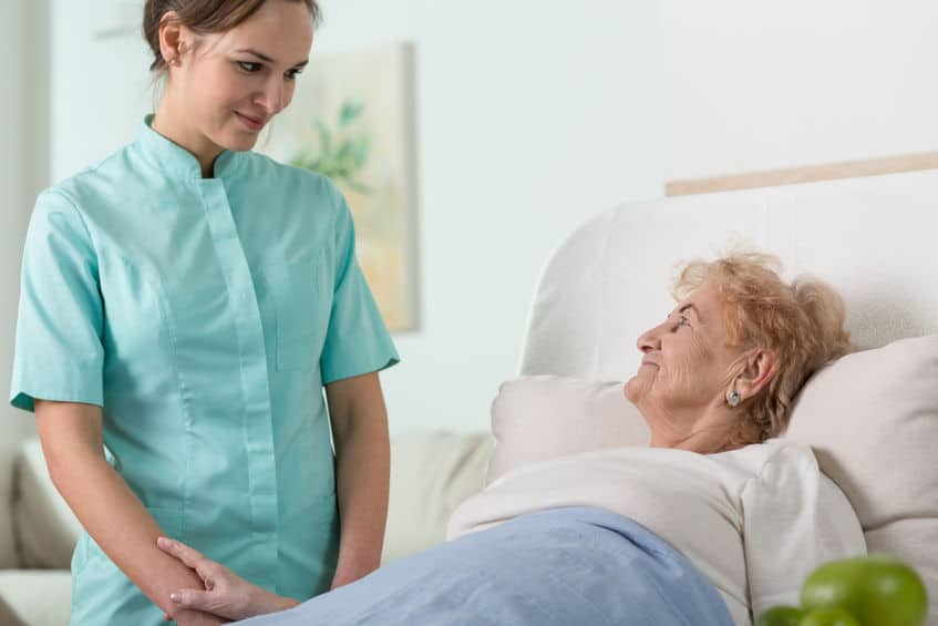 Nurse standing at elderly woman's bedside