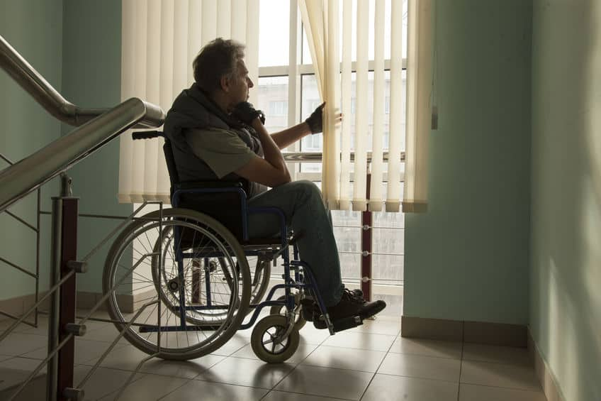 elderly man sitting in wheelchair looking out window