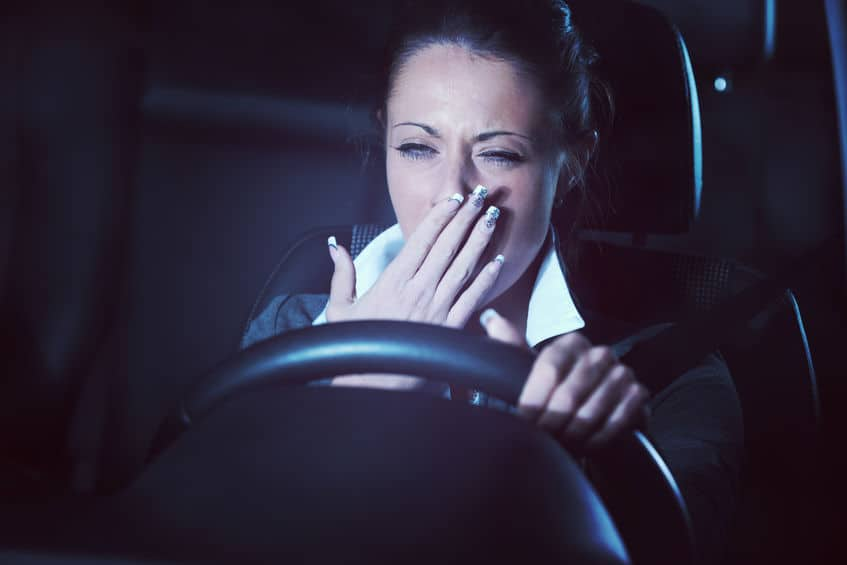 tired woman yawning while driving a car at night