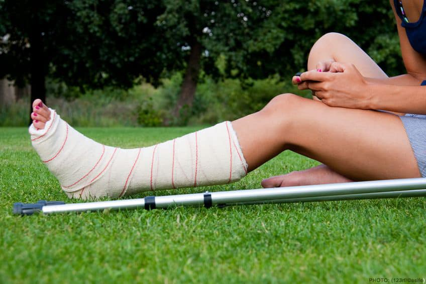 girl with a cast on her broken leg sitting in the grass on her phone. crutches lying down at her side.