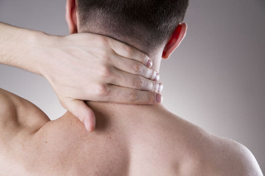 person holding the back of their neck in pain