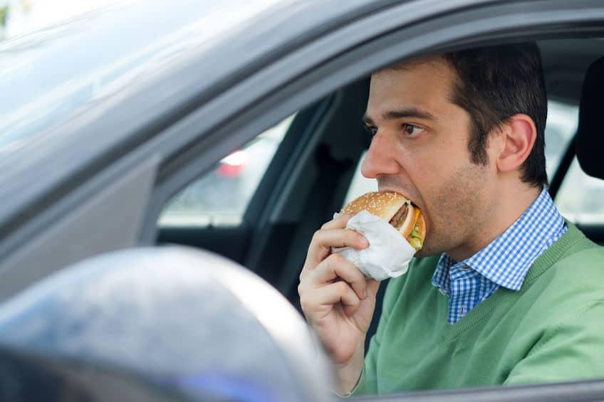 man eating a burger while driving a car