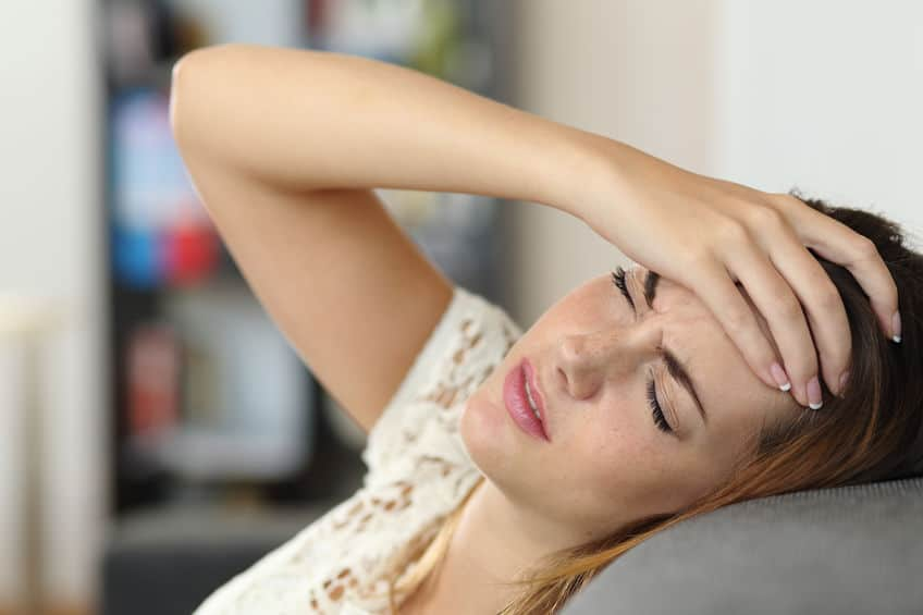 woman on a couch with a headache from a concussion and hand on her forehead