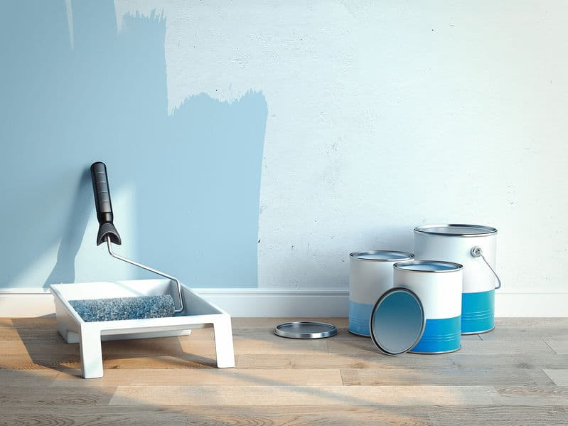 Paint cans and paint roller brush near light blue walls, 2 cans are opened, 1 is closed