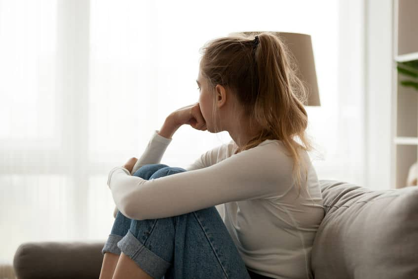 woman sitting on couch looking out the window