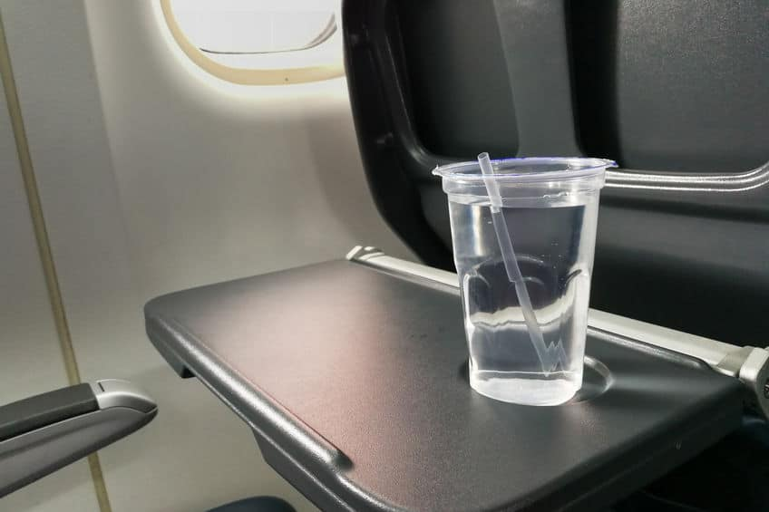 a cup of water sitting on a tray table in an airplane