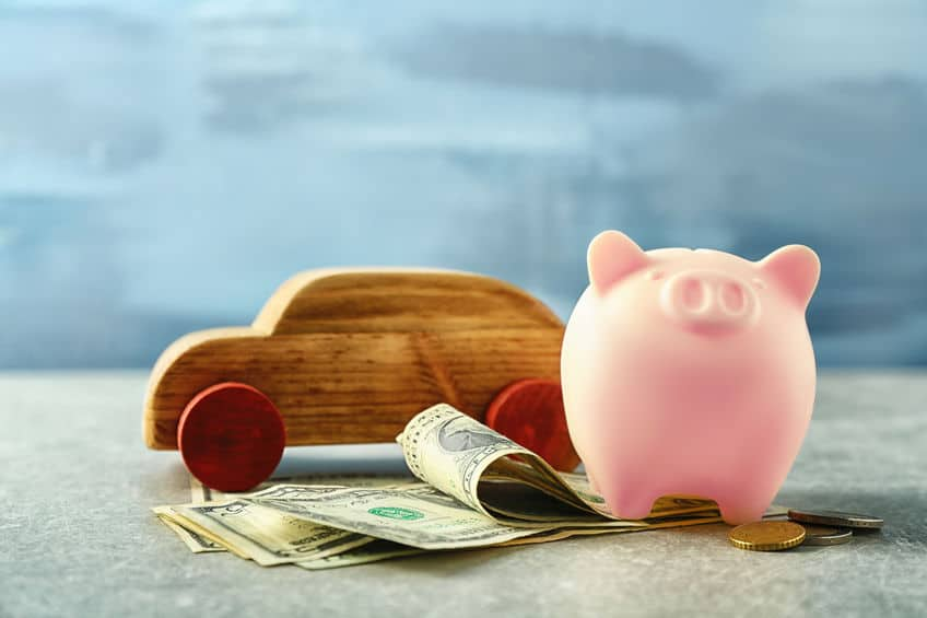 piggy bank with money under it and a wooden car on the table to demonstrate car insurance