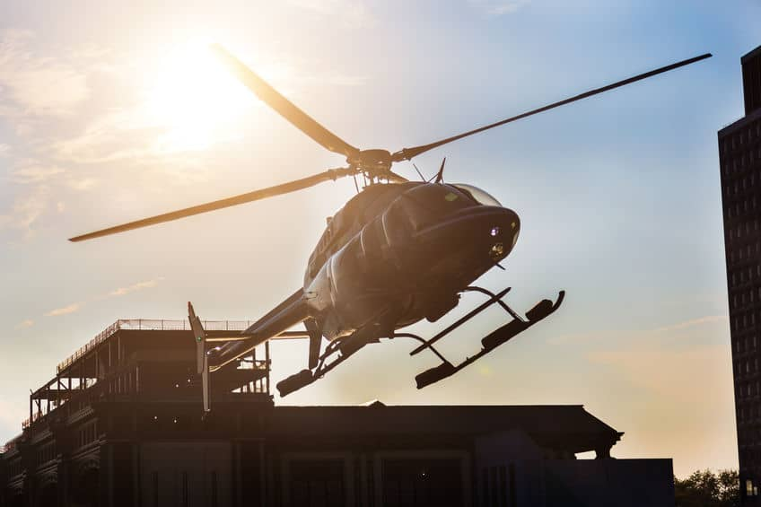 a helicopter taking off with sun in the background