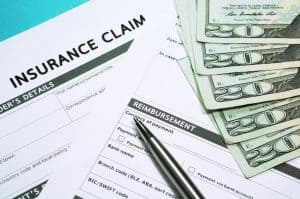 car insurance claim forms with a pen and money on a table