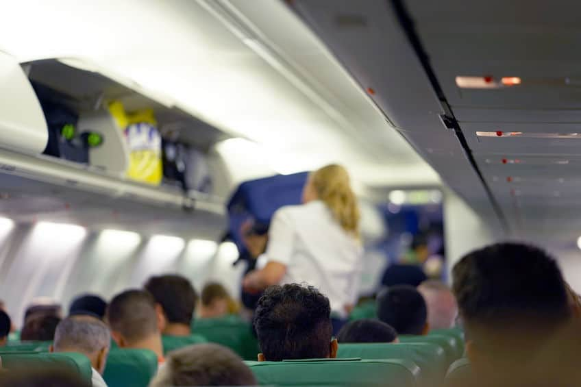 a flight attendant lifting luggage into the overhead compartment in the cabin of an airplane filled with passengers