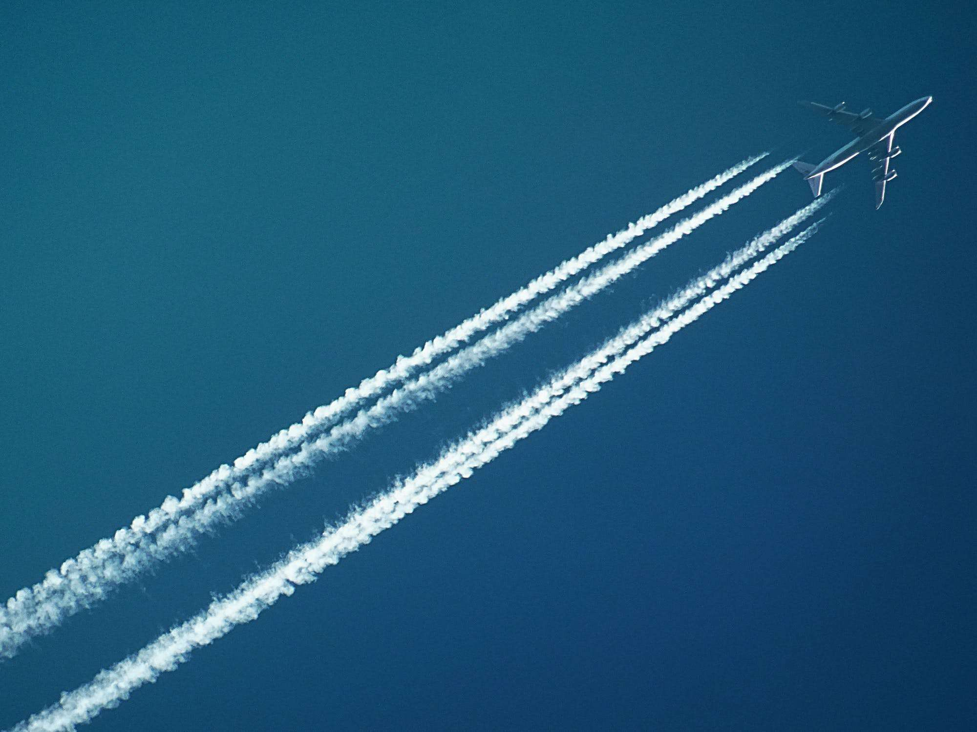 and airplane in the air with contrails
