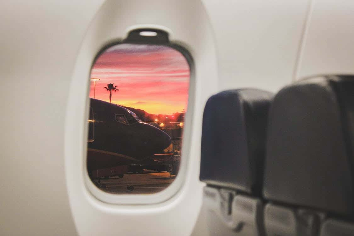 the view from a passenger's perspective looking out the window of an airplane at another plane and a sunset in the background