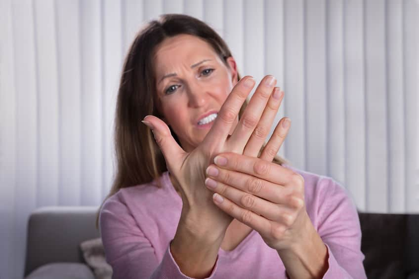 a woman holding her hand out in front of her suffering from pain in her wrist after a car accident