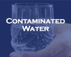 Contaminated Water - blue over a hand holding a glass with water in it