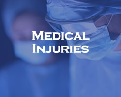 Medical Injuries - blue overlay on two doctors with scrubs and PPE on